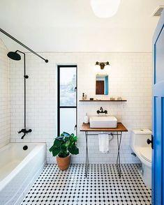 Cheio de personalidade, este banheiro apostou nas referências retrôs! Os ladrilhos no piso quebraram com decoração all-white junto com os metais pretos e a porta pintada em azul!