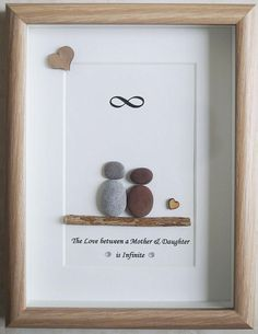 This is a beautiful small Pebble Art framed Picture of Mother & Daughter - The Love between a Mother & Daughter is Infinite handmade by myself using Pebbles, Driftwood, White Heart Size of Picture incl Frame : approx. 22cm x 17cm This Picture is finished and only available as shown in