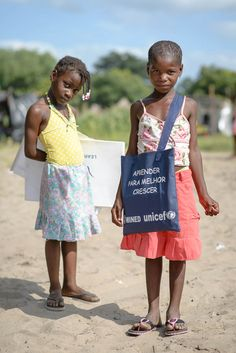 Six-year old Paulina (r) just received her UNICEF learners' kit at the Chiaquelane accommodation centre in Chokwe. Her best friend Marcia, also 6, is still waiting for hers. These kits contain copy books, pens, pencils, and other school materials. UNICEF distributed 600 of them at the Chiaquelane camp this past week.  -- © UNICEF Mozambique/2013/Alexandre Marques