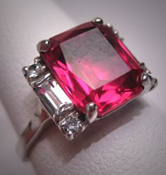 A Gorgeous Antique Faceted Verneuil Ruby and White Sapphire Ring, Vintage Art Deco Era, circa 1920-30's in White Gold. This antique ring holds a stunning antique verneuil ruby gemstone at its center measuring about 10 x 8mm in an emerald cut. The stone has magnificent color and beautiful facets to catch the light. The setting is beautifully made and adorned with white sapphires on the sides and is made of white gold with openwork detailing.