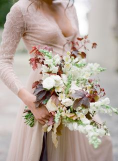 Anemone, ranunculus, and bold mahogany leave wedding bouquet: http://www.stylemepretty.com/2016/10/01/blush-pink-wedding-dresses/ Photography: Jose Villa - http://josevilla.com/