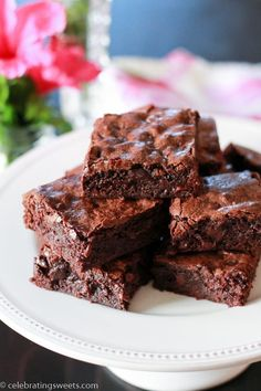 Brownies on a white plate with pink flowers in the background.