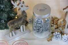 Christmas table decoration. Reindeers, pineapple and snowed firs in jars