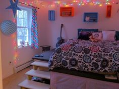 Teenager's room decor. Bed on a raised platform. Colorful wall crates. Lighting w/ holiday string lights