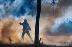A protester is silhouetted in teargas during clashes with riot police during a demonstration against the French government's labour reforms