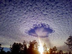 This is a rare meteorological phenomenon called a skypunch. When people see these, they think it's the end of the world. Ice crystals form above the high-altitude cirro-cumulo-stratus clouds, then fall downward, punching a hole in the cloud cover.