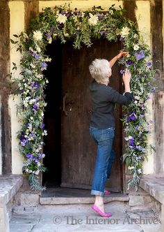 Artist and flower arranger Caroline Ede decorating the entrance to her Herefordshire cottage with flowers.