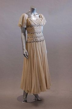A rhinestone studded gown, late 1940s-early 1950s; the midriff adorned with raised silver curleques. Via Kerry Taylor Auctions.