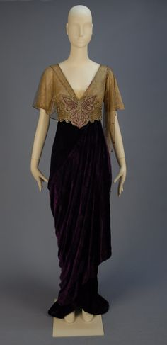 "TRAINED VELVET BELLE EPOCH GOWN with JEWELED BODICE 1913. Lush royal purple panne silk having short sleeve silk lace V-neck bodice asymmetrically draped in gold metallic mesh, high jeweled midriff band with center clear and magenta paste butterfly, hobble skirt layered over short train. Label ""Joseph 632 Fifth Avenue New York CYCLAMEN"" Front"