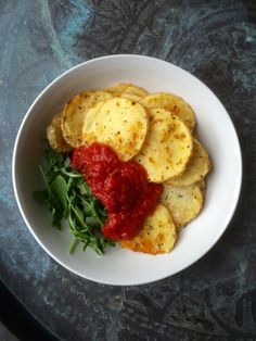 Thinly sliced oven roasted potatoes seasoned with cayenne, oregano, nooch, and lemon juice with arugula and tomato sauce