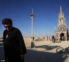 A man dressed as a priest outfit walks away from the 'Photo Chapel'