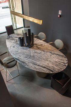 ovaler Tisch aus Marmor mit puristischer Leuchte - ruhige Kombination in Grau und Messing