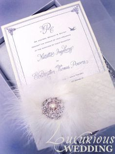 Bejeweled Purple Wedding Invitation with Crystal Brooch and Feathers via www.LuxuriousWedding.com/articles/carciofi_design.html