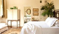 White linen bed with white furniture, black headboard, hanging art, and wooden brown hues