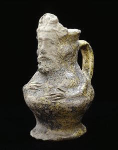 Miniature Kingston-type ware jug. Kingston-type ware miniature anthropomorphic jug with moulded bearded face applied at the rim, opposite the handle. The arms and fingers of the figure are also applied and incised.  Date 1241 AD - 1350 AD