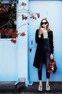 Chiara Ferragni  of The Blonde Salad rocks overalls with a stripe tee, oversized black coat, and Dior sneakers.