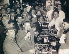 Pizza en La Boca, comiéndola a la vieja usanza, de pie y con un vino moscato. Las pizzas no siempre fueron redondas. Foto 1929