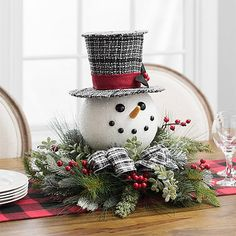 Frosty the Snowman has nothing on this little guy. Bring festive fun to any table in your home with this Pine and Snowman Head Floral Arrangement.         Arrangement measures 20L x 20W x 17H in.         Crafted of foam, plastic, and polyester         Pine and berry floral arrangement         Snowman head design         Features plaid top hat and bow         Hues of red, green, white, and black         Care: Dust with soft, dry cloth.        This item is available at Kirklands.com only, not…