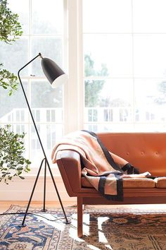 Brown leather sofa, rug, greenery, bright large windows and chic side lamp | Interiors | The Lifestyle Edit
