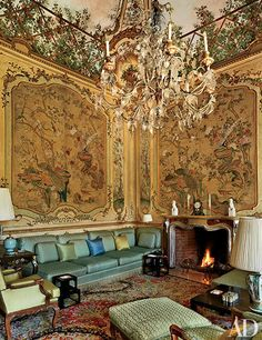 A sofa designed by Stephane Boudin spans one end of the piano nobile's main salon, which is decorated with panels of antique Chinese wallpaper; the Italian chandelier dates from the 18th century.