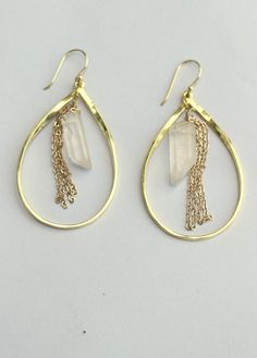 """Gold oval hoops surround a crystal and tasseled gold chain for an earring that mixes the elements of stone and metal perfectly. Measures 2 1/4"""" in length including hook . $30.00"""