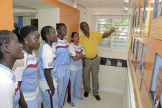 Kyshona Knight, Deandra Dottin, Kycia Knight, Tremayne Smartt and Anisa Mohammed listens to Barbados and West Indies legend Cammie Smith explain pictures of famous players on the wall.