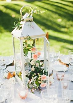 Cute! Transform a metal lantern into a decorative terrarium by filling it with greenery and blooms. #weddingideas @onelovephoto