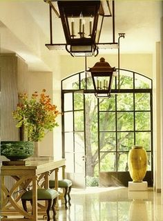 Love the simplicity, doors and lantern light fixtures... and the large vase