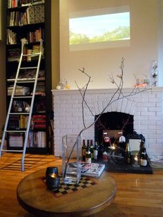 love the bookshelf with the ladder and the fireplace with the candles