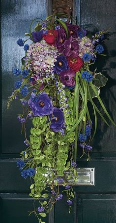 Welcome spring with our Gramercy Garden Swag, an arrangement brimming with seasonal florals, including dominant shades of purple, touches of blue and green, and a slight hint of red and pink.