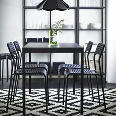A black dining table with black chairs and a black-brown storage combination