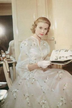Grace Kelly reading on set of High Society (1956). This is a gorgeous ballerina dress embroided with flowers in silk and satin and poet sleeves. This dress worn by Tracy Lord (Grace Kelly) was designed by Helen Rose, an Oscar-winning costume designer. Rose also designed Kelly's wedding dress, used when she married Prince Rainier.