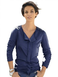 Shirt mit dezentem Glanz und modisch interessanter Ausschnittlösung. Effektvoll sind die glitzernden Motiv-Nieten auf den Schultern und der feminine Volant im Vorderteil. Interessante Knopfmanschette und Raffungen an den Schultern. Figurbetonte Form, Länge in Gr. 38 ca. 64 cm. Obermaterial: 95% Viskose, 5% Elasthan, Obermaterial 2: 98% Polyester, 2% Elasthan, waschbar...