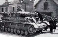 A Panzer 4 getting some engine maintenace made while the crew has time to relax.