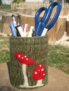 A #felted sweater sleeve with mushrooms felted on and pulled over a can.