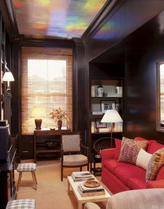 Under the unique iridescent painted ceiling in the brown study stand many Hadley designs. One is the coffee table made from wood and lacquered to simulate the parchment surface of Jean-Michel Frank's 1930s prototype. The red sofa's fabric is from Roger Arlington.   - HouseBeautiful.com
