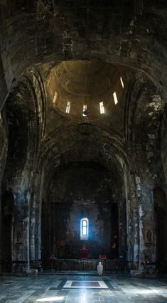 A woman praying in the dark and cool interior of Tatev monastery in Armenia.