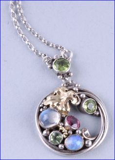 Dorrie Nossiter. An Arts and Crafts gem set pendant, unmarked, the circular frame enclosing a cut vine leaf, tendrils and beading, set with peridots, moonstone, an opal, and a pink tourmaline, 2.4 cm diameter, on a later chain. Sold by Dreweatts.
