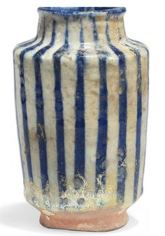 AN INTACT KASHAN POTTERY ALBARELLO   CENTRAL IRAN, 12TH CENTURY   Of typical form with slightly flaring walls on short ring foot, with short neck and rounded lip, the decoration with cobalt-blue lines on white ground, with old inventory number to foot