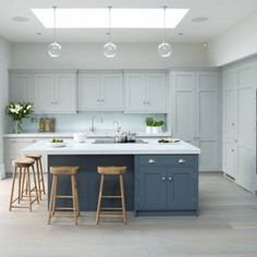 a light grey kitchen, a muted blue kitchen island and white countertops