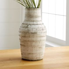 Hand formed on a potter's wheel, the Lati vase is handcrafted in the Philippines from locally sourced clay. Incised with alternating straight and inclined lines, the cream-glazed vase has a rustic, modern feel.