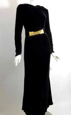 1930s black silk velvet bias cut evening gown with a silk sash.  The belted waist is trimmed in the front with goldtone metal mesh accent.  Gown zips up the left side.  The back has a shallow 'V' with 2 strips across the opening.  Shirred at shoulder and neckline.  Loop & fabric covered buttons fasten up the long sleeves from the wrist to the forearm.  Sleek and elegant