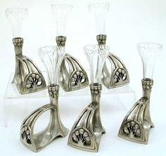 WMF NAPKIN RING VASES               Manufacturer WMF   Designer    Description A set of six polished pewter Art Nouveau napkin rings with cut glass posy vases   Country of Manufacture Germany   Date 1906