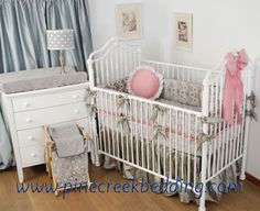Gender Neutral crib bumper and dust ruffle in grey fabrics with a pink ruffle on the sheet and pink accessories that can be switched to blue for the next baby