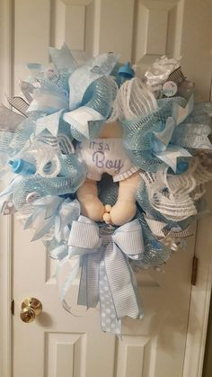 24 its a boy wreath, made with 21 light blue deco mesh. It has various blue and grey wired ribbon as embellishments. It has baby bottles, pacifiers, rattles as accents. Baby Shower Bouquet, Baby Shower Niño, Baby Shower Vintage, Baby Shower Parties, Baby Shower Themes, Baby Door Wreaths, Baby Boy Wreath, Baby Tea, Baby Shawer