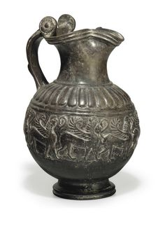 AN ETRUSCAN BUCCHERO PESANTE TREFOIL OINOCHOE  CIRCA MID 6TH CENTURY B.C.  The spherical body molded with a relief frieze of nine sphinxes moving right, each with a sickle-shaped wing, her tail raised, tongues descending on the shoulders, the strap handle with a reclining hound in top view, the rotellae molded with rosettes 12 3/8 in. (31.4 cm.) high