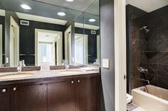 Elegant Master Bathroom with granite counter top and flooring.  Double undermount sinks, single lever faucets, recessed lighting. Tub/shower and bidet to the right and private water closet to the left.Floor to ceiling granite on walls of tub/shower.