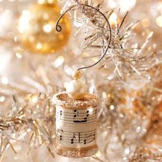Wooden Spool Christmas Ornament - Wooden spools are repurposed into beautiful little Christmas ornaments using mod podge, sheet music, glitter, beads and wire. Try other craft paper, paint, and embellishments to suit your needs! SOO cute!♥
