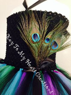 This tutu dress is LOADED with beautiful vibrant peacock feathers! All tops are 100% fully lined so you cannot see through them except the