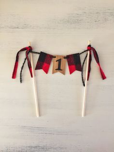 Lumberjack First Birthday Cake Topper, Cake Smash Top off your little guys rustic lumberjack cake smash with our adorable cake topper! -Each bunting flag is made of high-quality oak veneer and sealed for protection. Center flag has a black cardstock 1 and end flags are adorned with buffalo plaid fabric. All flag backs are plain wood, tied together with black twine. -Wooden flags measure 1 x 1.5 each. Wooden poles measure 6 high. See our lumberjack style crown and cake topper set (shown in…